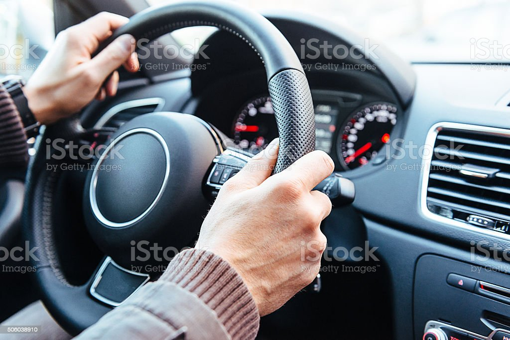 Man driving modern car, holding steering wheel in city traffic stock photo