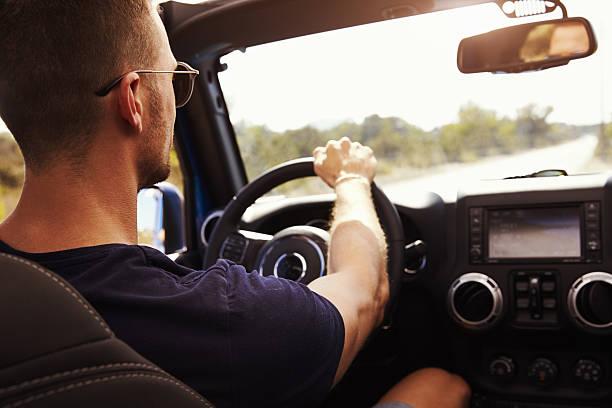 man driving open top car on country road - mietwagen stock-fotos und bilder