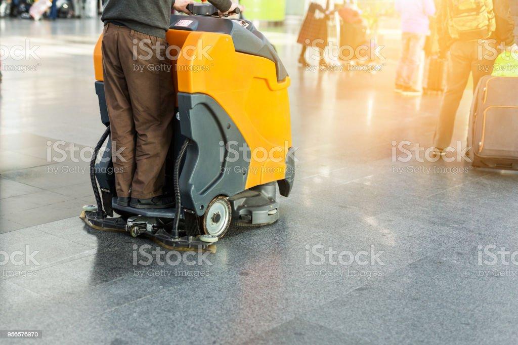 Mannen kör professionell golvrengöring maskin på flygplats eller järnvägsstation.  Golvvård och rengöring servicebyrå - Royaltyfri Affär Bildbanksbilder