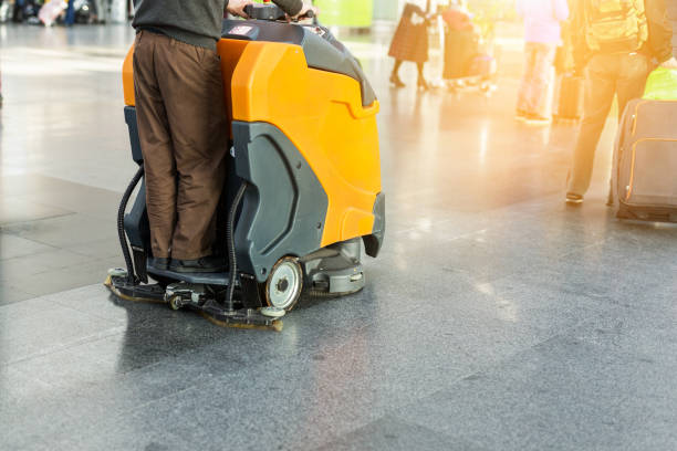 Man driving professional floor cleaning machine at airport or railway station.  Floor care and cleaning service agency stock photo