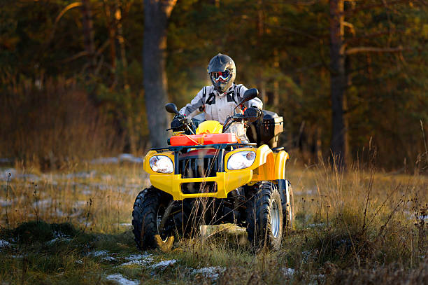 Man driving quad bike Horizontal portrait of a man in helmet and safety goggles looking into the camera while sitting on all-terrain vehicle against snowy late autumn landscape. quadbike stock pictures, royalty-free photos & images