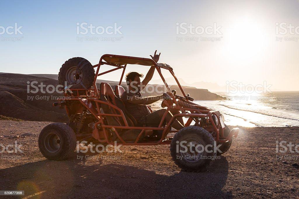Man driving quadbike in sunset. stock photo