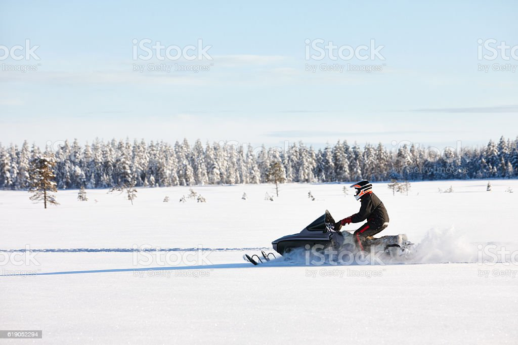 Man driving snowmobile in Finland stock photo