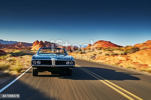man driving vintage car through desert in nevada