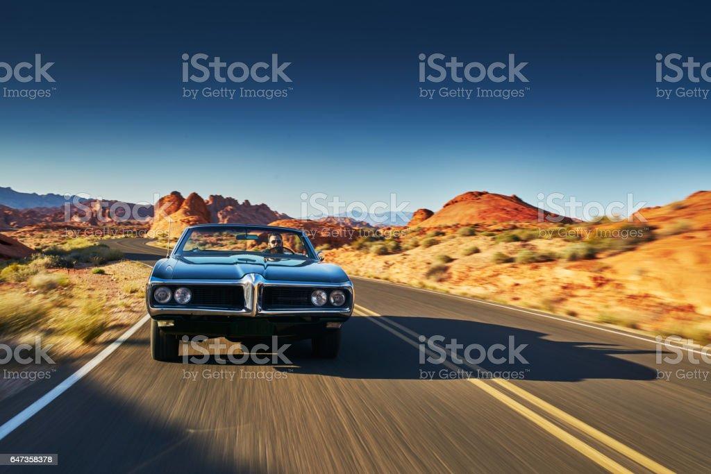 man driving vintage car through desert stock photo