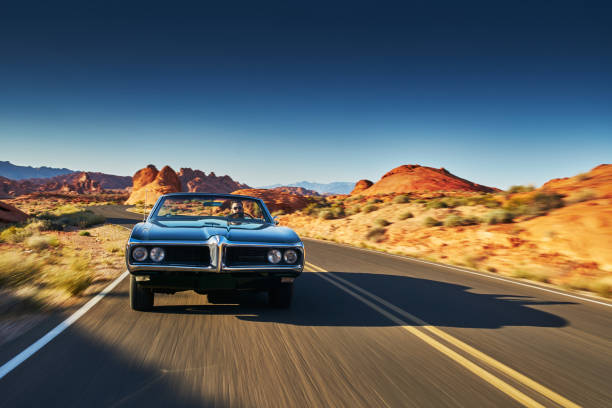 man driving vintage car through desert - classic cars stock photos and pictures