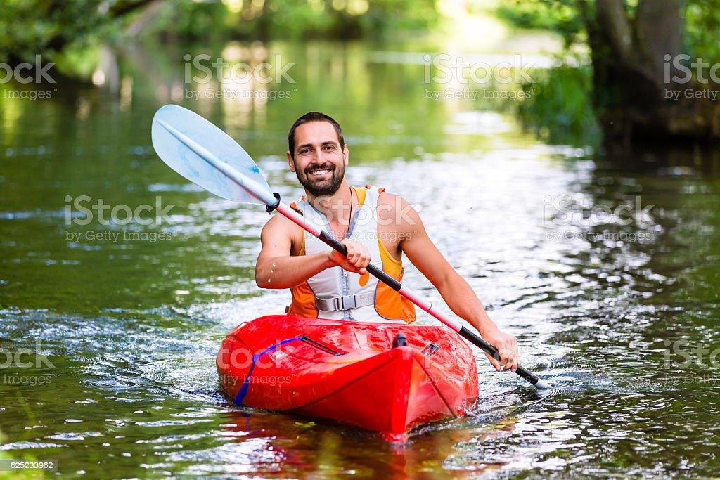man driving with kayak on forest river stock photo