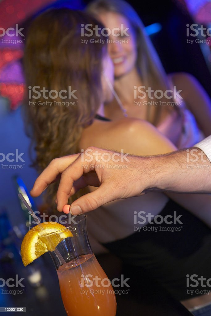 Man Drugging Woman's Drink In Bar stock photo