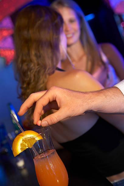 man drugging woman's drink in bar - 殺球 個照片及圖片檔