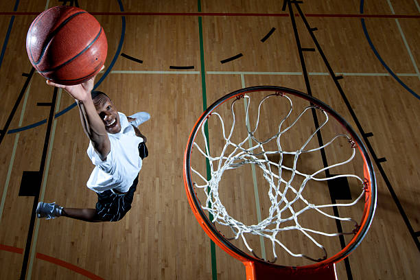 Man Dunking a Baskteball A young man dunking a basketball. Focus on the basketball. slam dunk stock pictures, royalty-free photos & images
