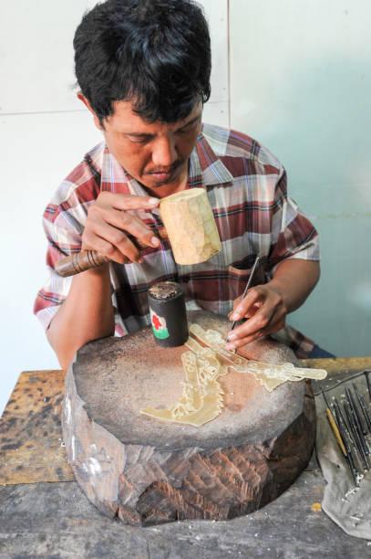 man during the manufacture of a wayang kulit - wayang kulit stock photos and pictures