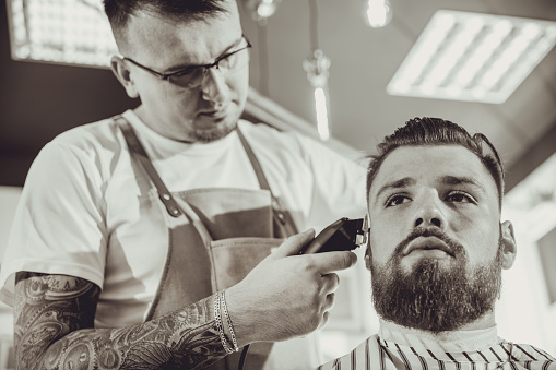 986804130 istock photo Man during trimming a beard in a barbershop in black & white stylization 986798500