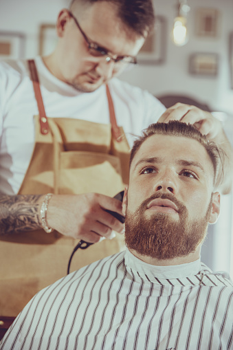 986804130 istock photo Man during trimming hair in a barbershop 1030927012
