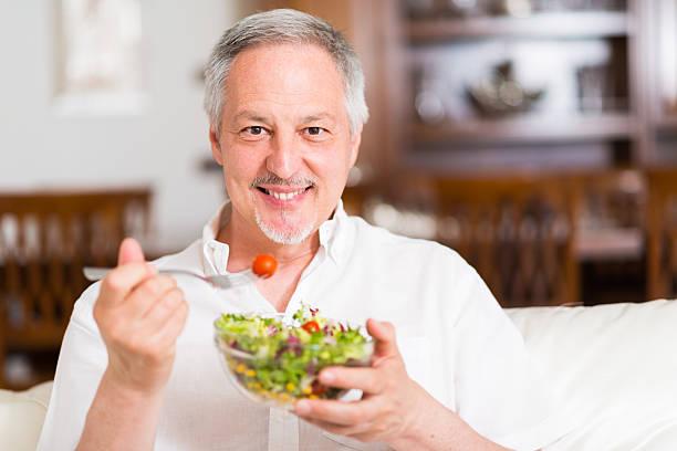 Man eating a salad stock photo