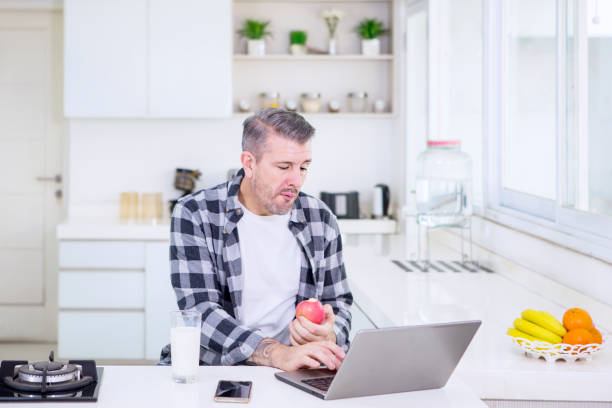 Man eating an apple while working in the kitchen stock photo