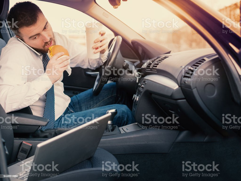 Mann einen Hamburger Essen und arbeiten sitzen sein Auto – Foto