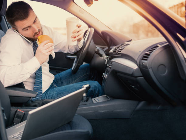 man eating an hamburger and working seated his car - detraction stock pictures, royalty-free photos & images