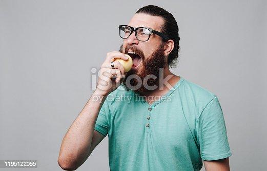 104545719istockphoto Man eating apple 1195122055