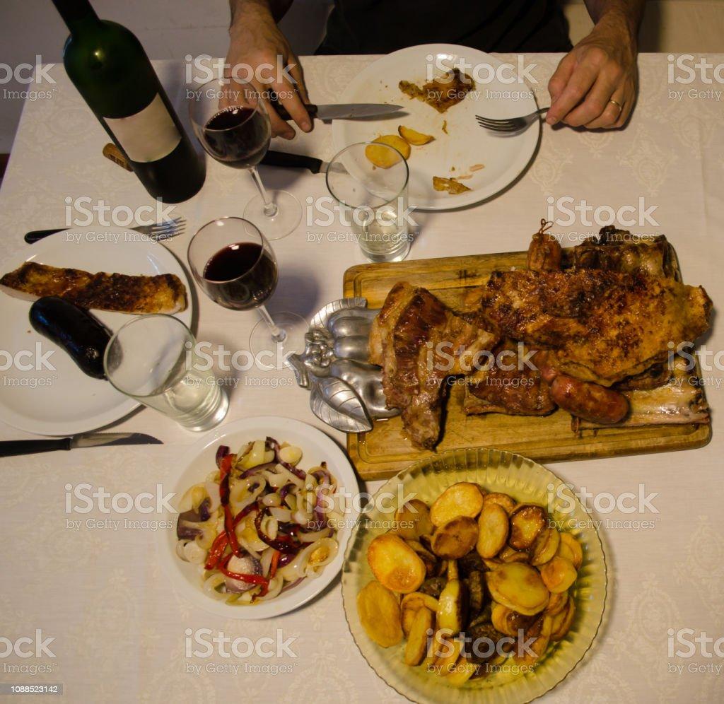 Hombre comiendo asado con patatas y cebolla. - foto de stock