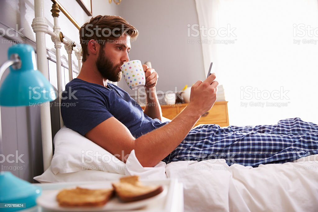 Man eating breakfast in bed while checking his smartphone stock photo