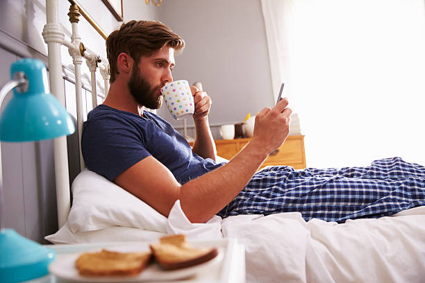 man eating breakfast in bed while checking his smartphone - day in the life series stock pictures, royalty-free photos & images