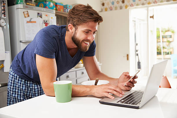 man eating breakfast in kitchen and using computer and phone - day in the life series stock pictures, royalty-free photos & images