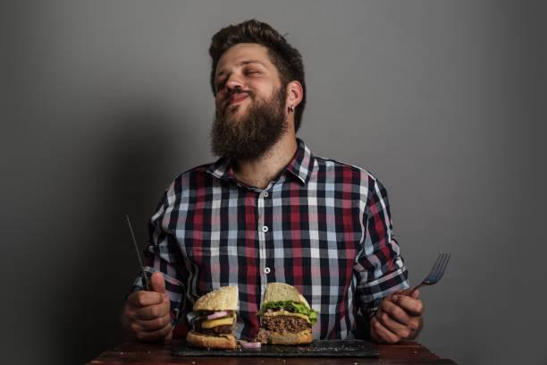 Homem comendo hambúrguer - foto de acervo
