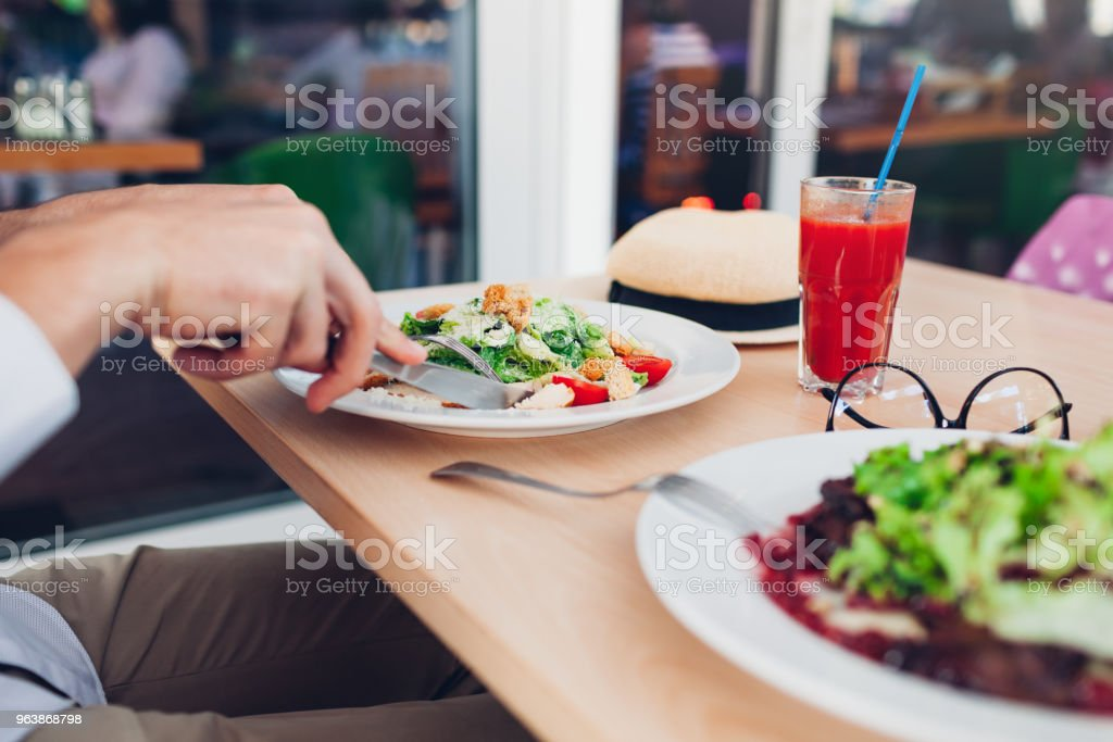Man eating Caesar salad in restaurant. Having tasty lunch. Healthy food concept. - Royalty-free Adult Stock Photo