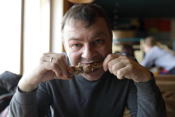 Hombre comer pata de pollo - foto de stock