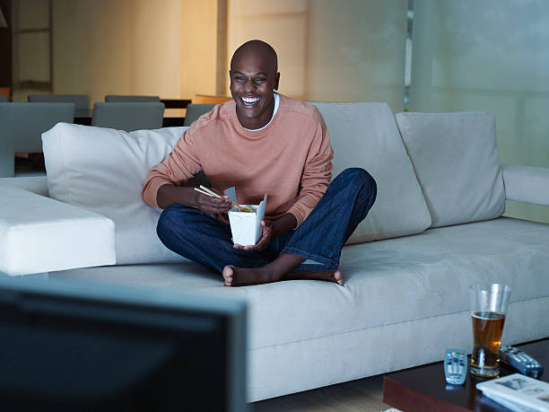Man eating Chinese food watching television  man cave couch stock pictures, royalty-free photos & images