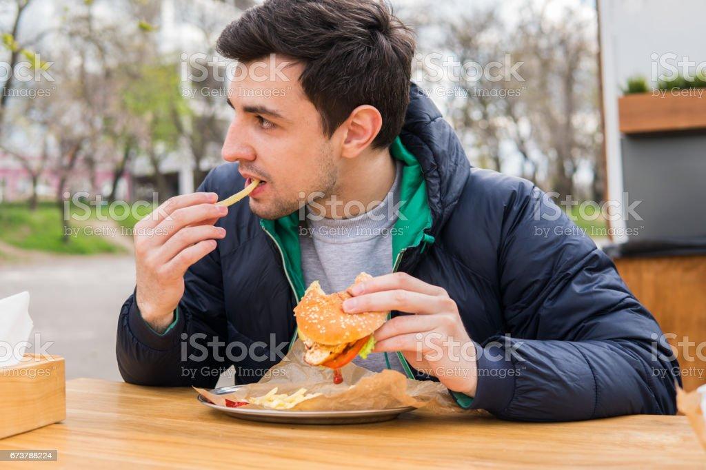 adam sokak gıda kafede hamburger ile kızarmış patates yeme royalty-free stock photo