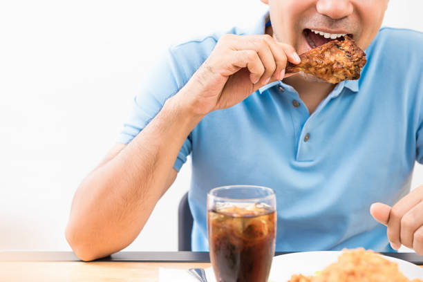 ein mann isst gegrilltes huhn in einem restaurant - schmaler tisch stock-fotos und bilder