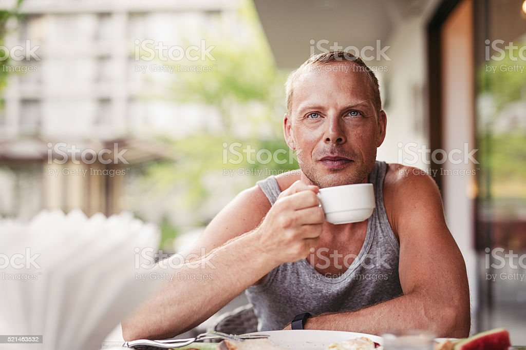 Man eating healthy breakfast and drinking coffee outdoors stock photo