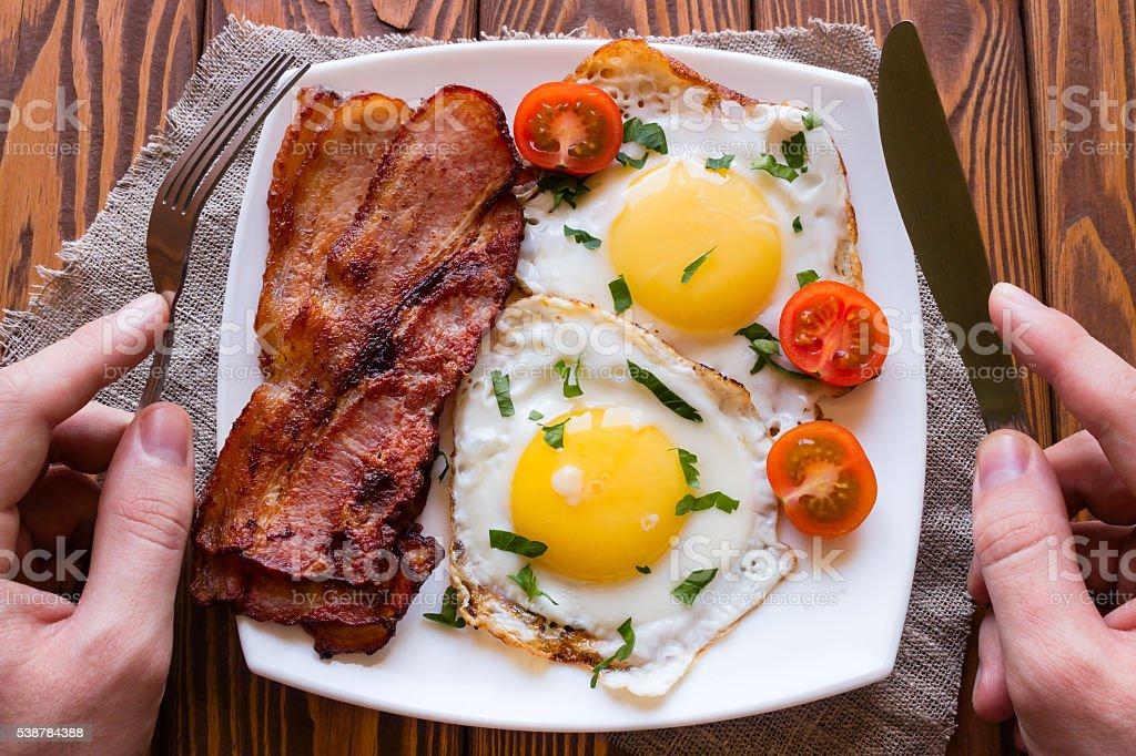 Mann Essen seiner Frühstück mit Rührei, Speck und Tomaten – Foto