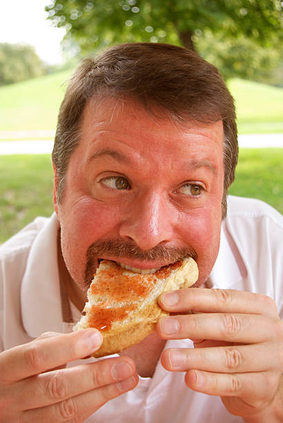 man eating jellied bread - mikefahl stock pictures, royalty-free photos & images