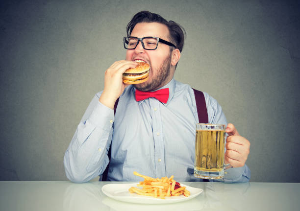 man eating junk food drinking beer - metabolic syndrome stock photos and pictures