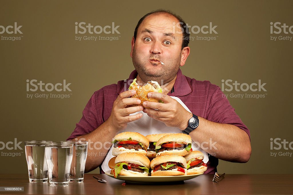 Man eating many burgers stock photo