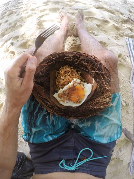 Mann isst Nudeln aus Kokosnuss – Foto