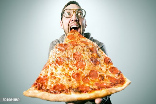 An excited adult man gets ready to take a bite out of a ridiculously large slice of pepperoni pizza, a look of excitement and joy on his face.  Horizontal image with copy space.