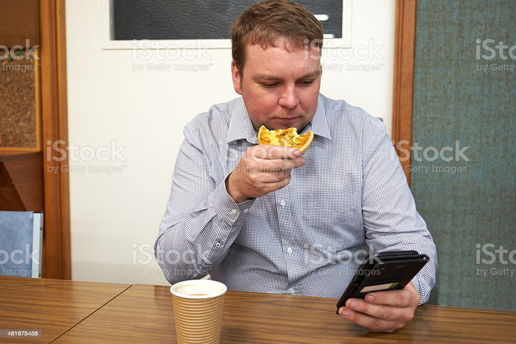man eating pie drinking coffee looking at phone stock photo