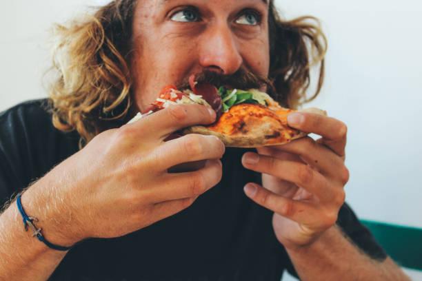 homem comendo pizza em um restaurante - comendo - fotografias e filmes do acervo