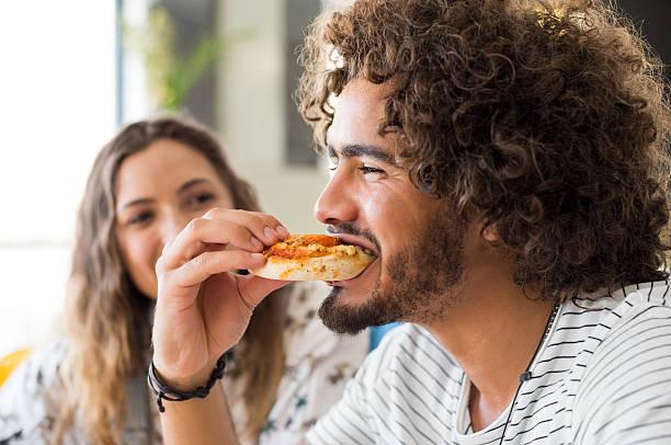 Homem comendo pizza - foto de acervo