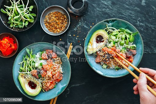 Man eating poke bowls with salmon, avocado, vegetables, sprouts and ponzu dressing on marble background