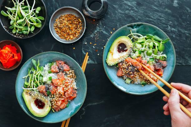 mann isst poke schalen mit ponzu-dressing - hawaiianischer salat stock-fotos und bilder