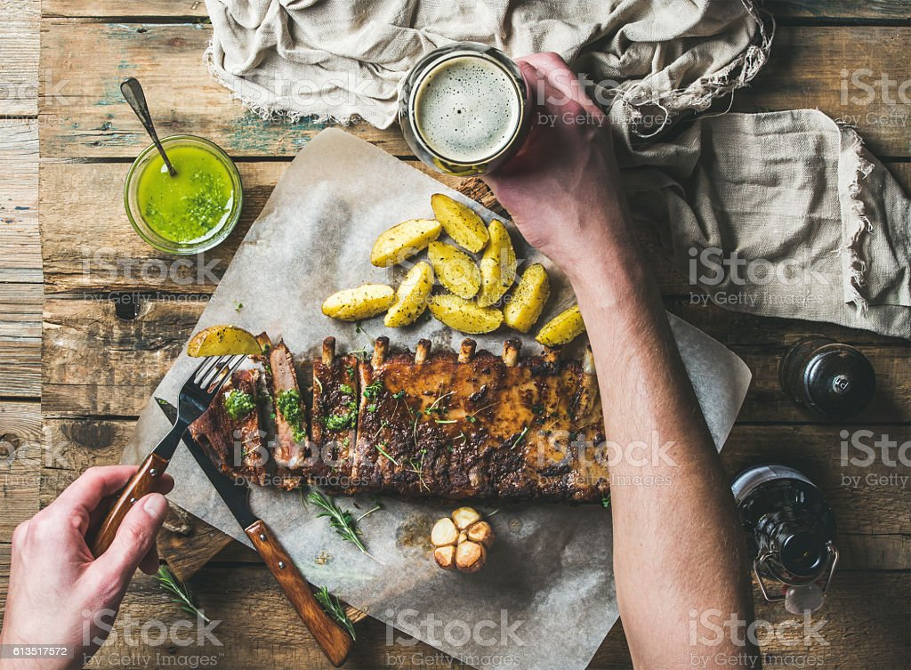 Man eating roasted pork ribs, holding fork and dark beer stock photo