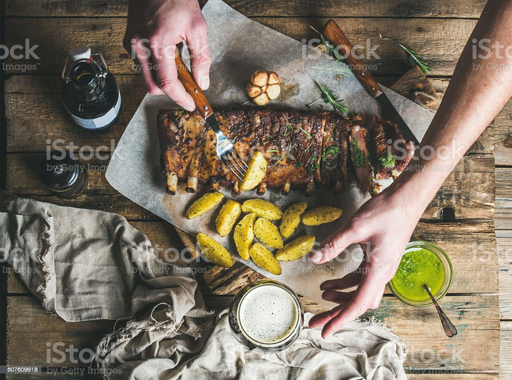 Man eating roasted pork ribs with garlic, holding fork stock photo