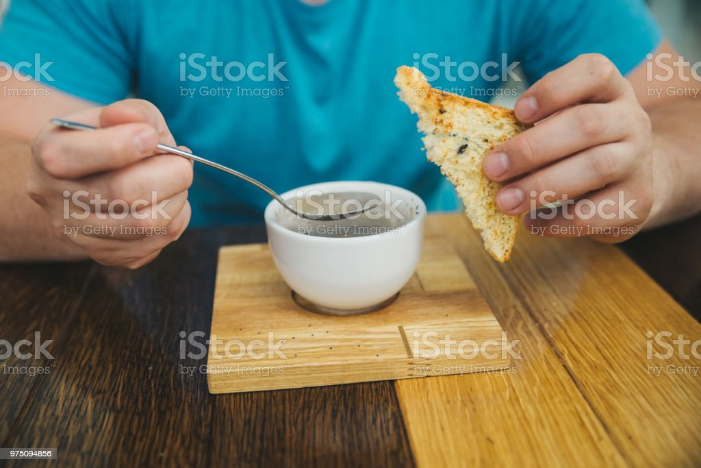 man eating soup in cafe. hold bread in other hand stock photo