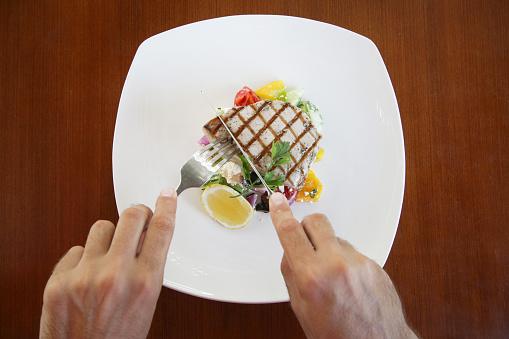 Man Eating Tuna Steak Top View-foton och fler bilder på Banta