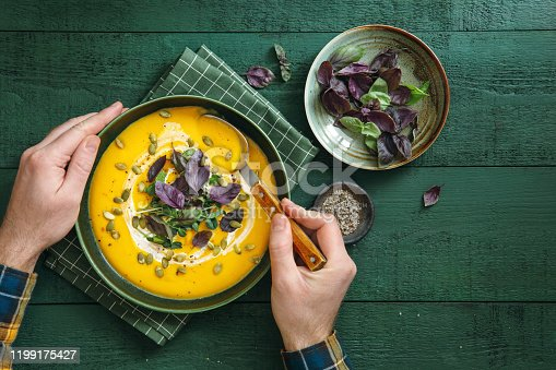 Man eating Vegan Creamy Roasted Pumpkin Soup on green wooden background