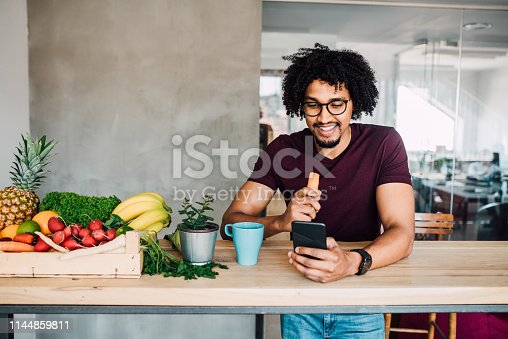 Young man having a healthy snack while studying